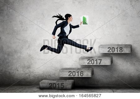 Picture of young businesswoman jumping on the stairs toward number 2018 while carrying financial chart