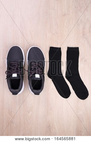 Top view black sport shoes with sock on wooden background