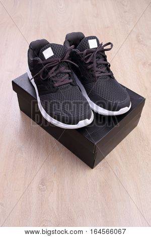 Black sport shoes with box on wooden background