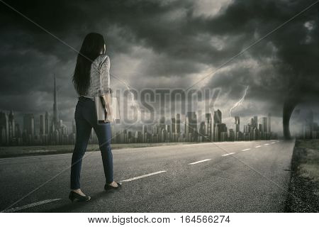 Back view of a female worker walking on the street while carrying a laptop computer with tornado on the sky