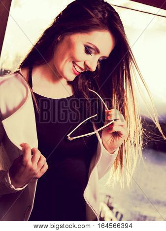 Fashionable girl long haired portrait. Stylish woman enlightened by sunbeams. Attractive elegant female positive smiling face expression