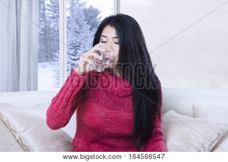 Portrait of young woman drinking a glass of water while sitting on sofa with winter background on the window