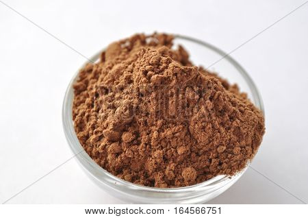 Raw cocoa (Theobroma cacao) powder in a glass bowl, closeup on white background