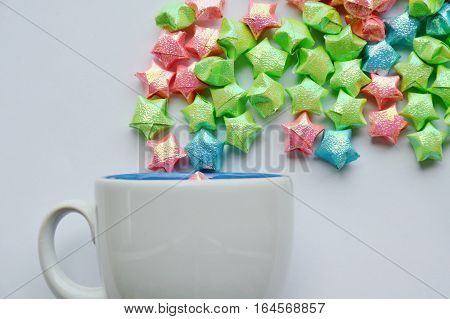 colorful star paper floating from coffee cup on white background