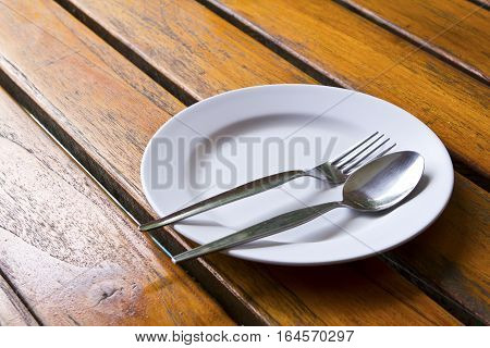 white plate with a spoon and fork