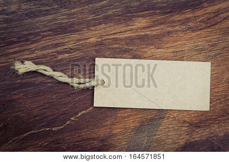 Blank price tag  with rustic wooden style background in vintage tone