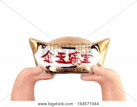 hands of plaster doll raised antique Chinese gold ingot isolated on white background, Chinese characters on gold ingot mean gold and jade filled the house or family of great wealth, auspicious gift and greeting in Chinese New Year