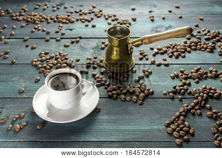A cup of black coffee on a wooden boards texture, with a vintage coffee pot,  beans scattered around, with copyspace. A horizontal design template for a cafe or shop