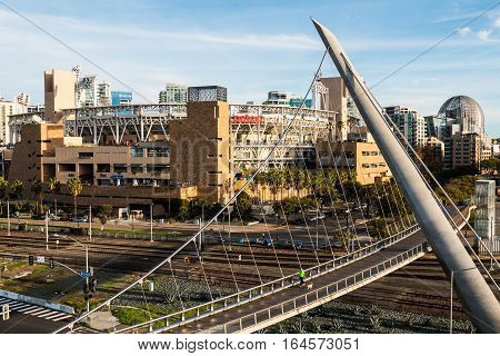 SAN DIEGO, CALIFORNIA - JANUARY 8, 2017:  The Harbor Drive pedestrian bridge, one of the longest self-anchored pedestrian bridges in the world, with Petco Park baseball stadium.