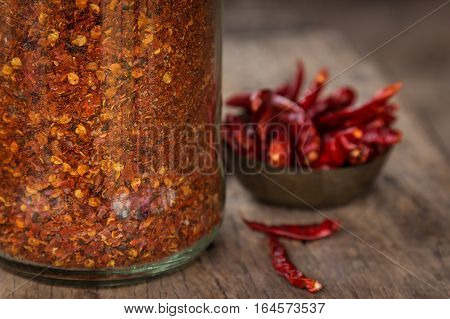 Chili powder on wooden spoon with rustic background