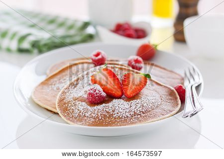 Homemade pancakes with fresh strawberry and raspberry on a white plate