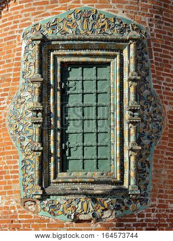 Window of old church with a frame of traditional Yaroslavl tiles and forged metal shutters