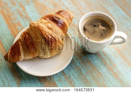 A photo of cup of dark coffee with a croissant, on a teal blue wooden board texture with copyspace