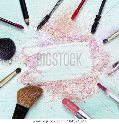 Makeup brushes and lipstick on teal blue background, with traces of powder and blush, forming a frame. Square template for makeup artist's business card or flyer design, with copyspace