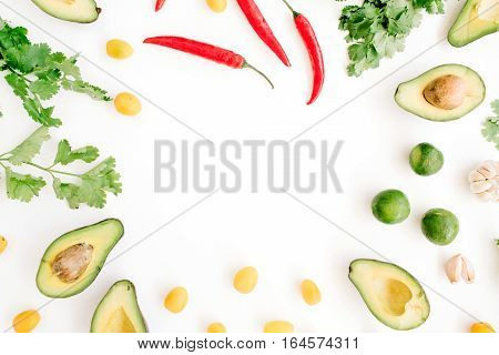 Frame made of raw food ingredients of guacamole: avocado chili pepper coriander cherry tomato lime garlic. Flat lay top view. Food concept.
