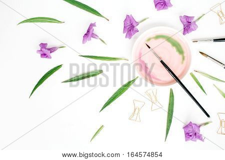 Artist workspace with watercolor paintbrushes golden clips green leaves. Flat lay top view