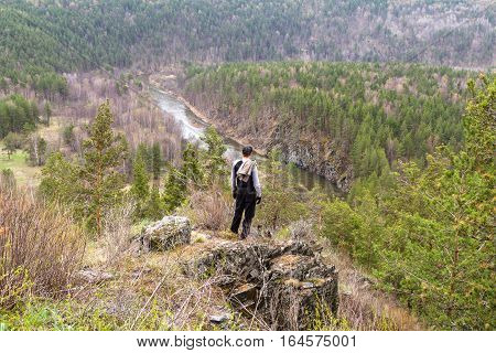 A man stands at the edge of the slope in the mountains of the Southern Urals.