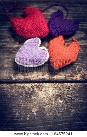 Valentine's Day. Colorful knitted hearts. Red heart on the dark old boards. Valentines day. Heart pendant. Red heart. Valentine cards. Eighth of March. International Women's Day. Toned image.