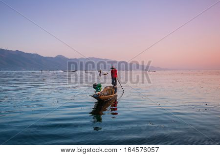 Local fishermen are fishing by boat in unique style, Inle lake, Myanmar