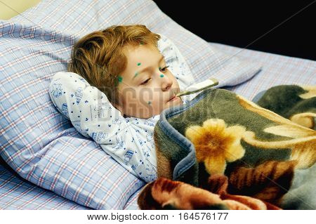 Sick child boy lying in bed with chicken pox