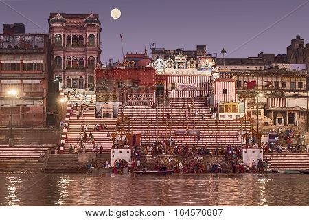 VARANASI, INDIA - NOVEMBER 15, 2016: A crowd of people bathing in the Ganges River before the sun comes up on the day after Dev Diwali. The moon is in the 'super moon' phase.