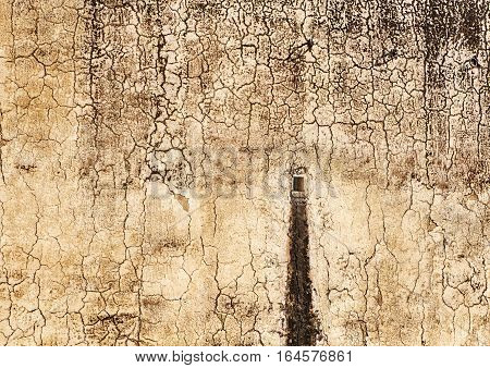 A drain hole shows a water stain on an interior wall of the Amber Fort near Jaipur India. The walls have a crackled pattern from the weather.