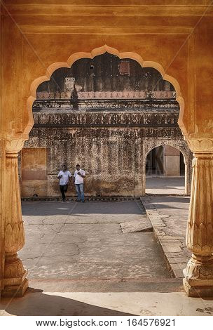 AMER, INDIA - NOVEMBER 18, 2016: Two men leaning up against a wall can be seen through an arch of the pavilion or baradari of the Man Singh Palace at the Amber Fort in the city of Amer near Jaipur, India.
