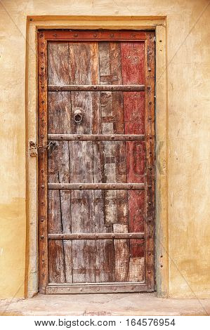 A locked door shows old weathered paint at the Man Singh Palace in the Amber Fort near Jaipur India.