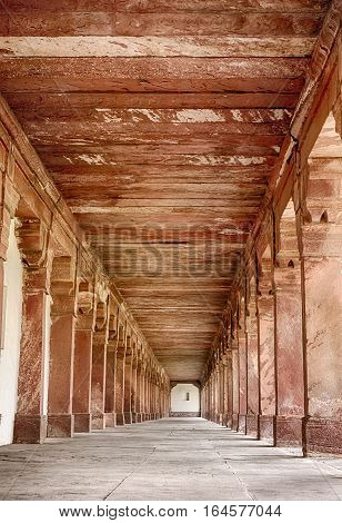 A long colonnade of red sandstone pillers is located at the ancient city of Fatehpur India.