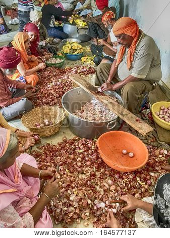 DELHI, INDIA - NOVEMBER 20, 2016: A group of volunteers is chopping garlic to prepare for the free community dining in the Langar Hall at the Gurudwara Bangla Sahib shrine in Delhi, India.