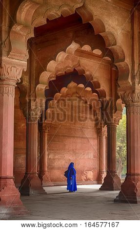DELHI, INDIA  NOVEMBER 19, 2016; An anonymous woman walks through the arches of the public audience hall (Diwan-i-Aam) in the Red Fort in Delhi, India. The red sandstone structure is typical of the Mughal architectural style of the 17th century.