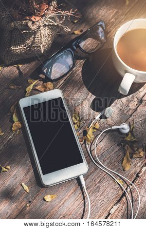 Cellphone with cup of coffee on wooden table in the garden
