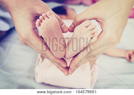 Baby's feet in mother's hand and heart shape