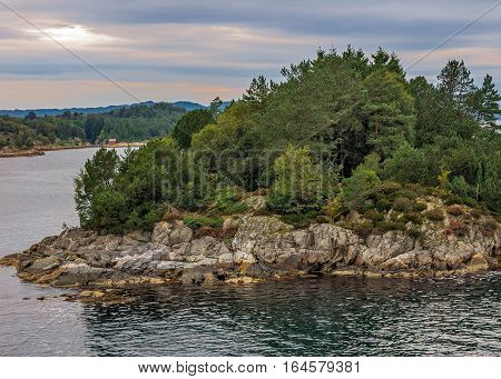 The rocky island in a fjord near Bergen Norway. Rainy summer evening the sky dark clouds. On granite boulders look beautiful green a little touched with yellow trees and shrubs .