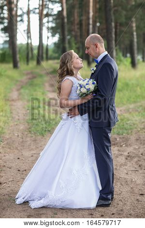 Lovely wedding couple in a forest are wolking