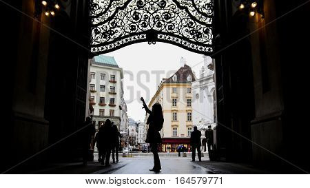 Woman using cell phone in hofburg Vienna, silhouette, wide angle, wide angle