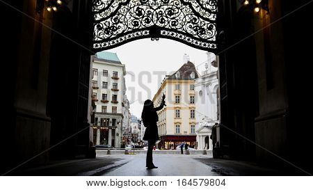 Woman using gadget in hofburg Vienna, silhouette, wide angle, wide angle