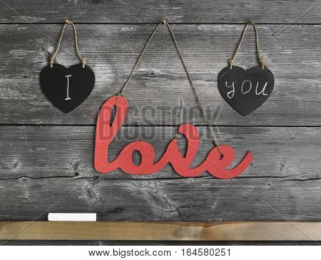 Greeting card Valentine. On gray wooden wall background two black chalk heart and an inscription love hanging from rope piece of chalk. Composition of inscription to Valentine's Day - I love you.