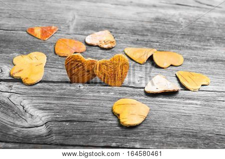 Greeting Card Valentine's Day. Two hearts from the bark of a tree on a gray wooden background. Many wooden hearts valentines nearby.