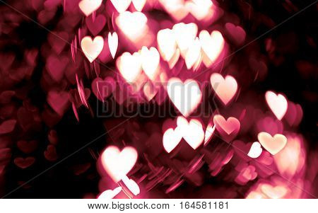 Defocused lights background. Heart bokeh. Bright colorful heart bokeh background. Multicolored blurry red and white hearts on a black background. Valentines Day illustration