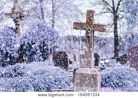 Concrete cross with crucifix in cemetery in winter. Snowfall.