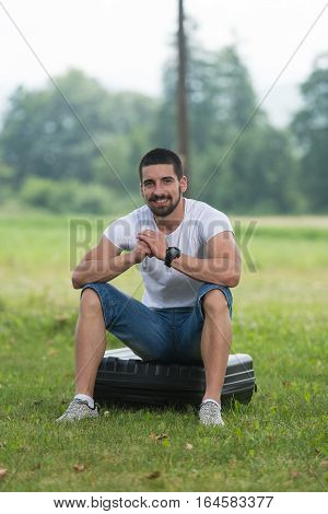 Man Sitting On Suitcase Of Drone
