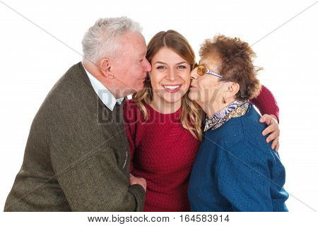 Picture of a happy elderly couple giving a kiss to their lovely granddaughter