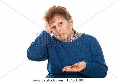 Close up photo of a senior woman's hands holding her pills