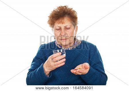 Portrait of a sick elderly woman taking her pills