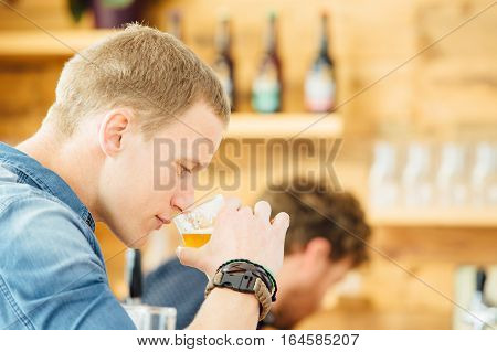 Side view of handsome blond man smelling craft beer. Bokeh