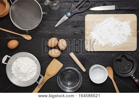 flour sprinkled with different wooden kitchen tools on black wood table