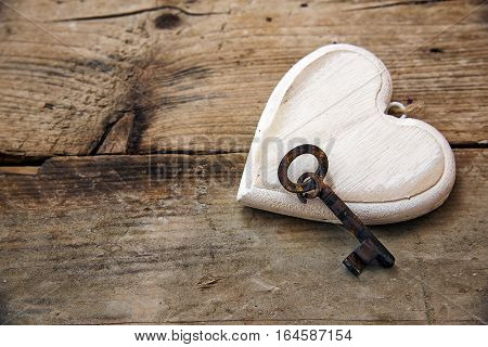 Heart shape made of white painted wood and an old key on rustic wooden boards concept for love valentine's and mother's day copy space