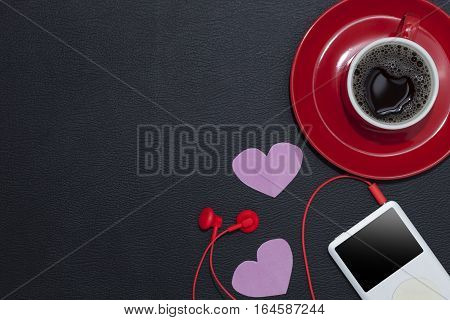 red coffee cup with music player and red earphone on black leather backgroundValentine's day concept.