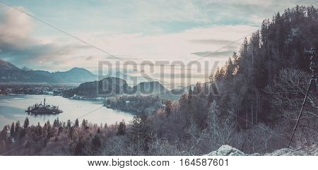 Panorama with lake Bled and the surroundings - Winter panorama at sunrise with the Bled lake and village surrounded by the Julian Alps and a camera mounted on a tripod
